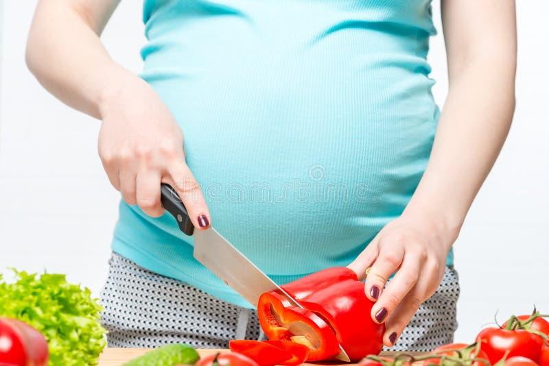 pancia di un primo piano e delle mani della donna incinta con un coltello immagine stock libera da diritti