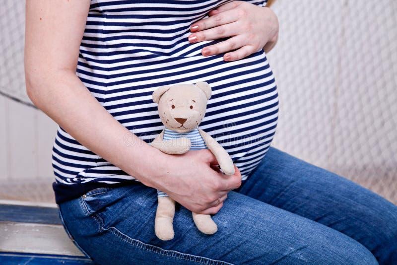 Pancia di una donna incinta con un orsacchiotto fotografia stock libera da diritti
