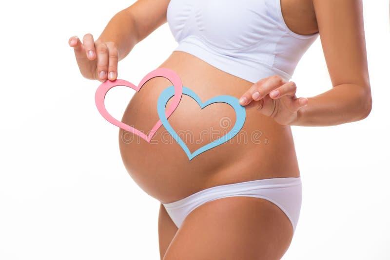 Pancia incinta con cuore blu e rosa primo piano orizzontale immagine stock
