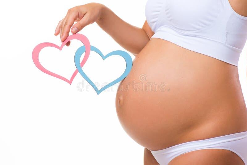 Pancia incinta con cuore blu e rosa primo piano orizzontale fotografie stock