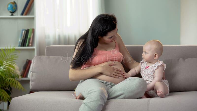 Pancia incinta della mamma commovente sveglia del bambino, prevedendo sorellina o fratello immagini stock libere da diritti