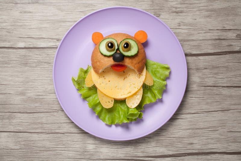 Panda φιαγμένη από ψωμί, τυρί και λαχανικά στο πιάτο και το γραφείο στοκ φωτογραφία