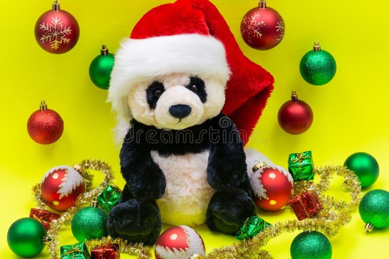Panda Bear, giocattolo con Red Christmas Babbo Hat circondato da Tinsel Garland e Vintage Ornamas su giallo brillante fotografia stock libera da diritti