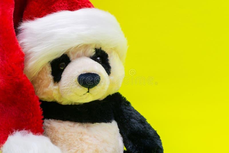 Panda Bear stuffed plush toy wearing Red White Christmas Plush Santa Hat on bright yellow background. Christmas, New Year royalty free stock image