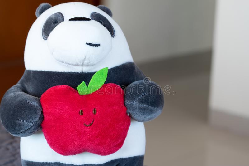 Panda plush toy holding a red apple with a happy face. Closeup with shallow depth of field and bokeh background stock images