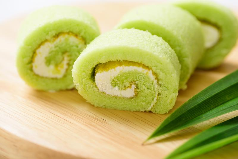 Pandan roll cake and fresh pandan leaf. On wooden background stock photo