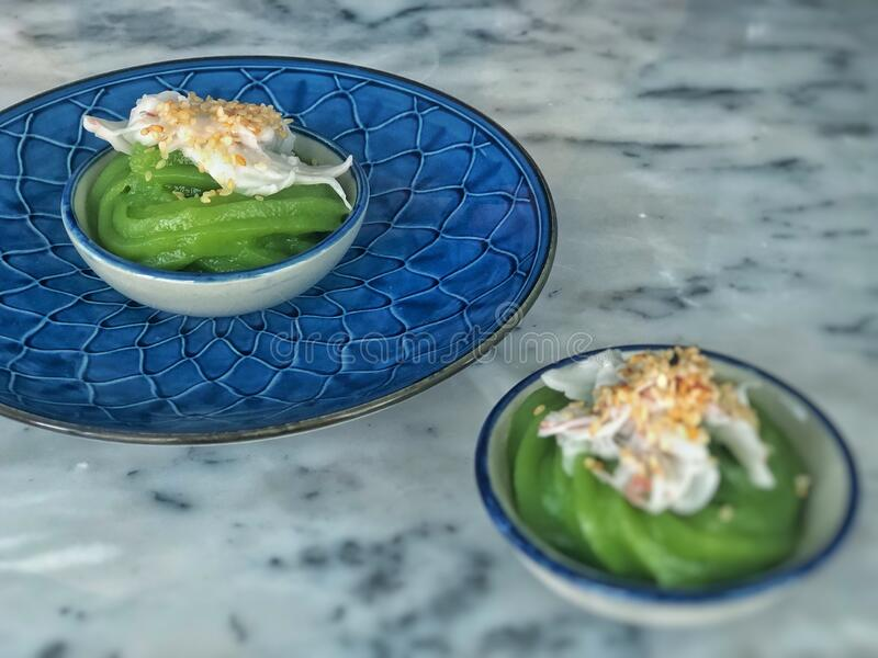 Pandan Sweet Pudding topping with coconut and white sesame, made of rice flour custard, Thai style dessert called Khanom Piakpoon,. Put in Thai style plate stock photography