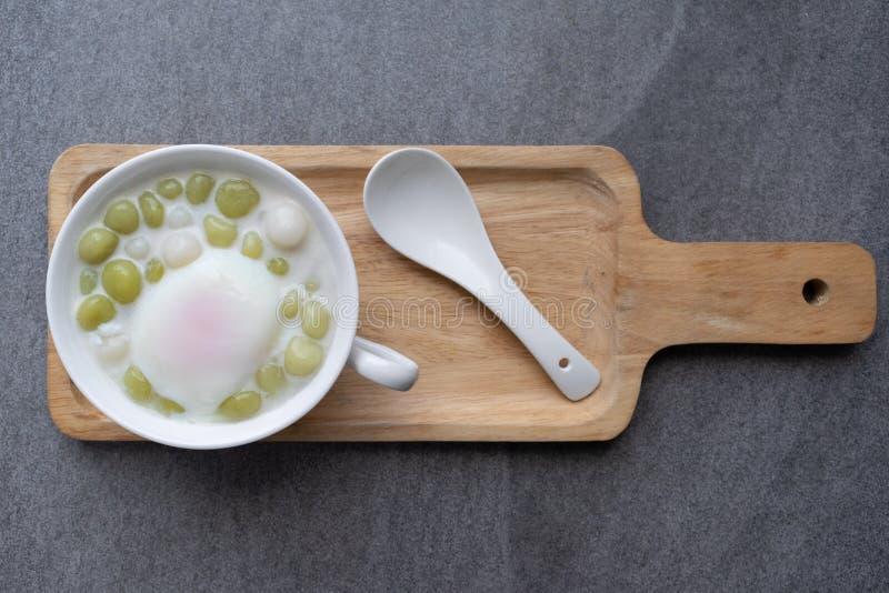 Pandan Thai glutinous rice balls Bua Loi in white bowl on table,Boiled egg royalty free stock images
