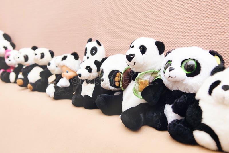 Pandas del juguete en fila, fondo beige imágenes de archivo libres de regalías