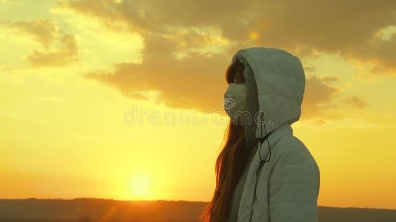 Pandemiskt coronavirus en fri kvinna som bär en skyddande medicinsk mask i solljus Skydd mot virus och fotografering för bildbyråer