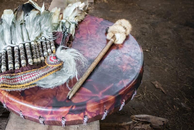 Pandereta antigua del amerindian, reproducción del palillo del tambor y un tocado de la pluma imágenes de archivo libres de regalías