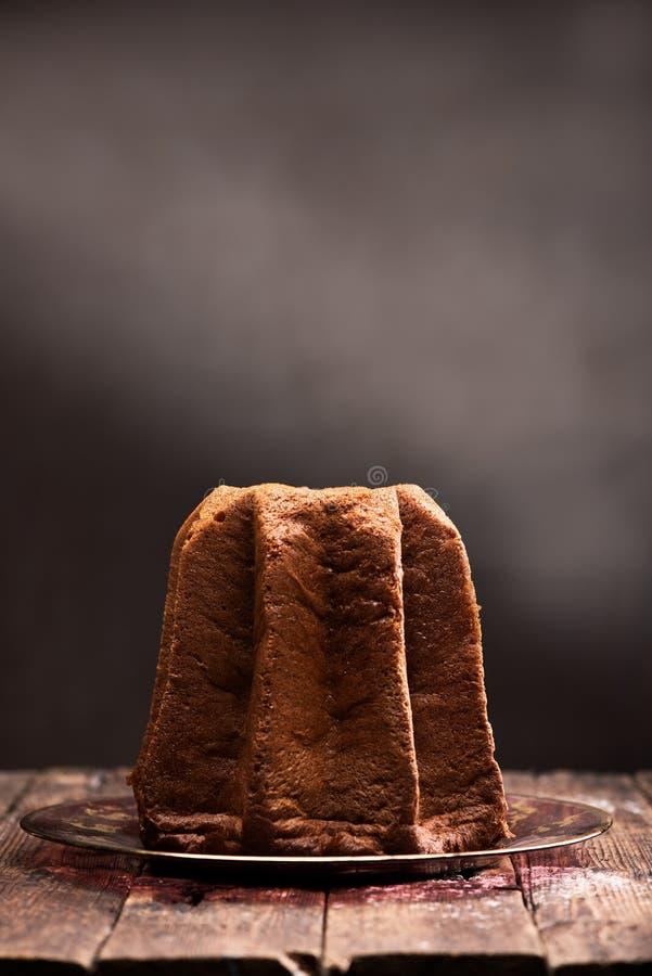 Pandoro mit Abstauben des Puderzuckers auf braunem Hintergrund lizenzfreie stockbilder