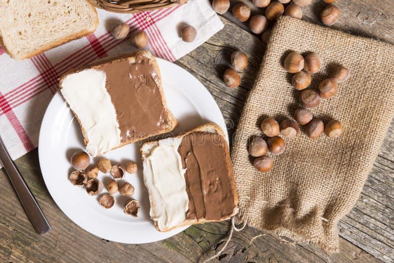 Pane affettato in piatto con la crema ed i dadi del cioccolato immagini stock libere da diritti