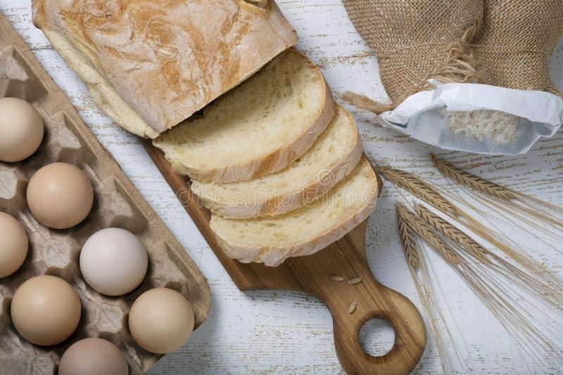 Pane affettato su un bordo di legno circondato dalle orecchie delle uova, della farina e del grano immagini stock libere da diritti