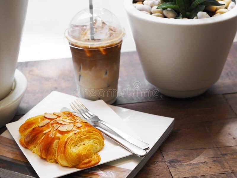 Pane amêndoas sobre a placa e o vidro brancos do café do latte do gelo em fotografia de stock royalty free