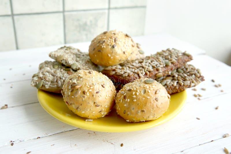 Pane bolos com as várias sementes na placa amarela na tabela de madeira branca imagem de stock