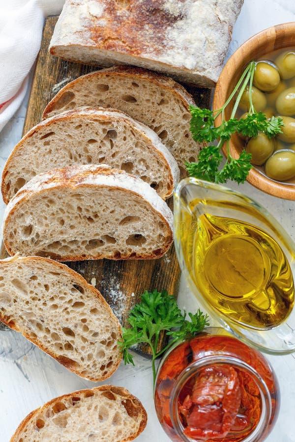 Pane casalingo con le olive, i pomodori seccati al sole e l'olio d'oliva fotografia stock