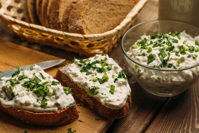 Pane casalingo dell'azienda agricola con la cagliata della ricotta ed erba verde e crema della cagliata in ciotola fotografia stock