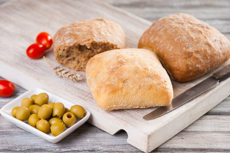 Pane casalingo, pomodori, olive e coltello immagine stock