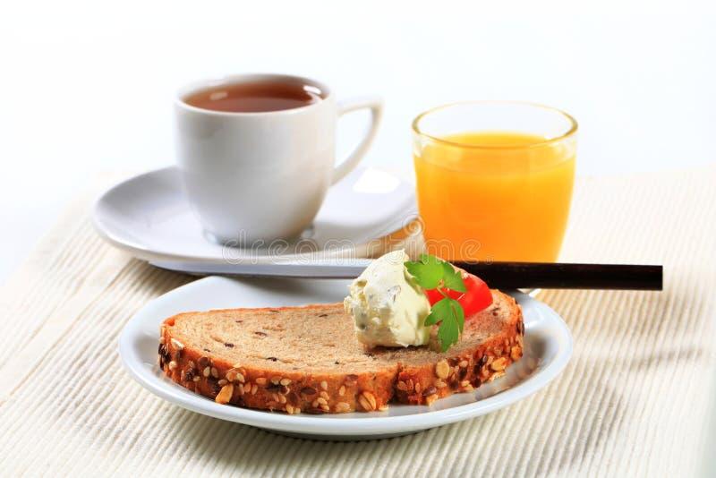 Pane con formaggio da spalmare, tazza di tè e succo d'arancia fotografie stock libere da diritti