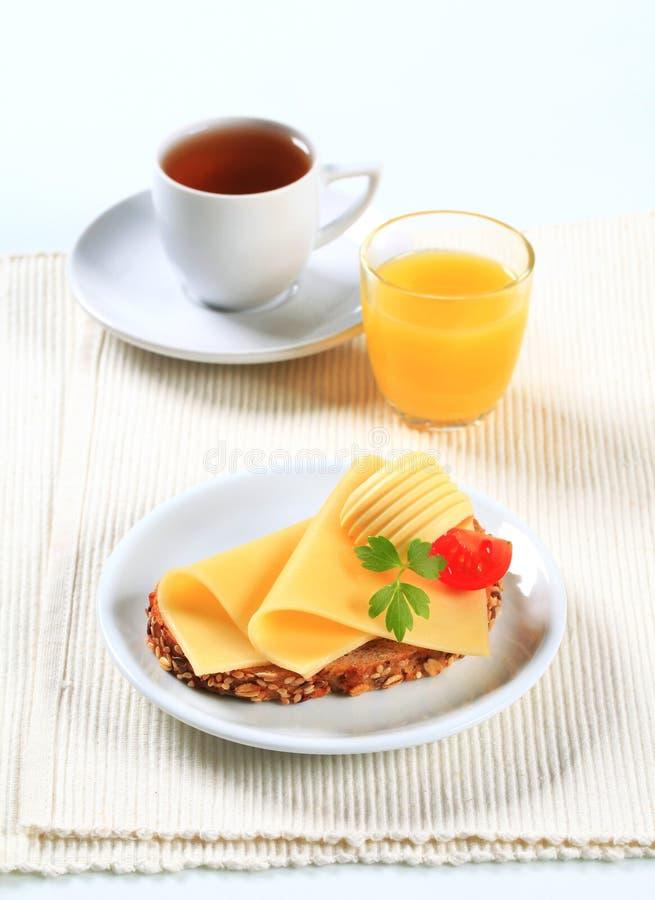 Pane con formaggio, tè nero e succo d'arancia fotografie stock