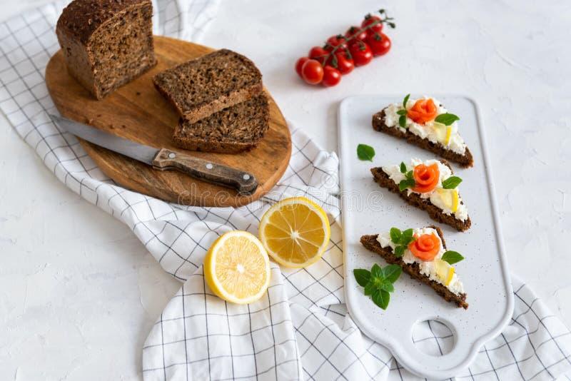 Pane con il formaggio cremoso di color salmone, del raccordo ed il limone freschi su fondo bianco, vista superiore Copi lo spazio fotografia stock libera da diritti