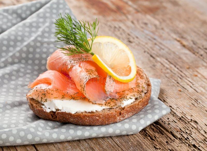 Pane con il raccordo di color salmone fresco su fondo di legno fotografia stock libera da diritti