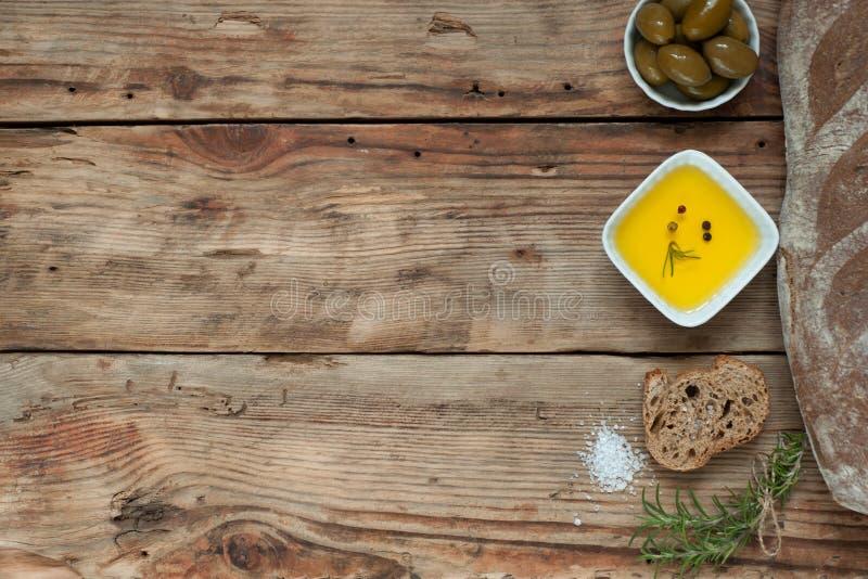 Pane con le erbe e l'olio d'oliva sui precedenti rustici fotografie stock