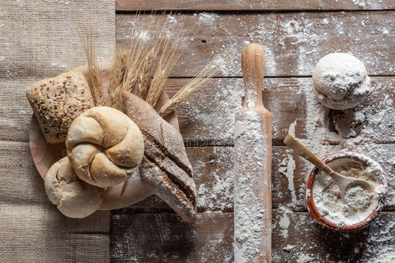 Pane con le orecchie e la farina del grano sul bordo di legno, vista superiore immagini stock libere da diritti