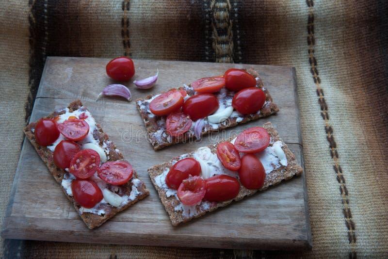 Pane croccante sottile della segale con burro ed i piccoli pomodori fotografie stock libere da diritti