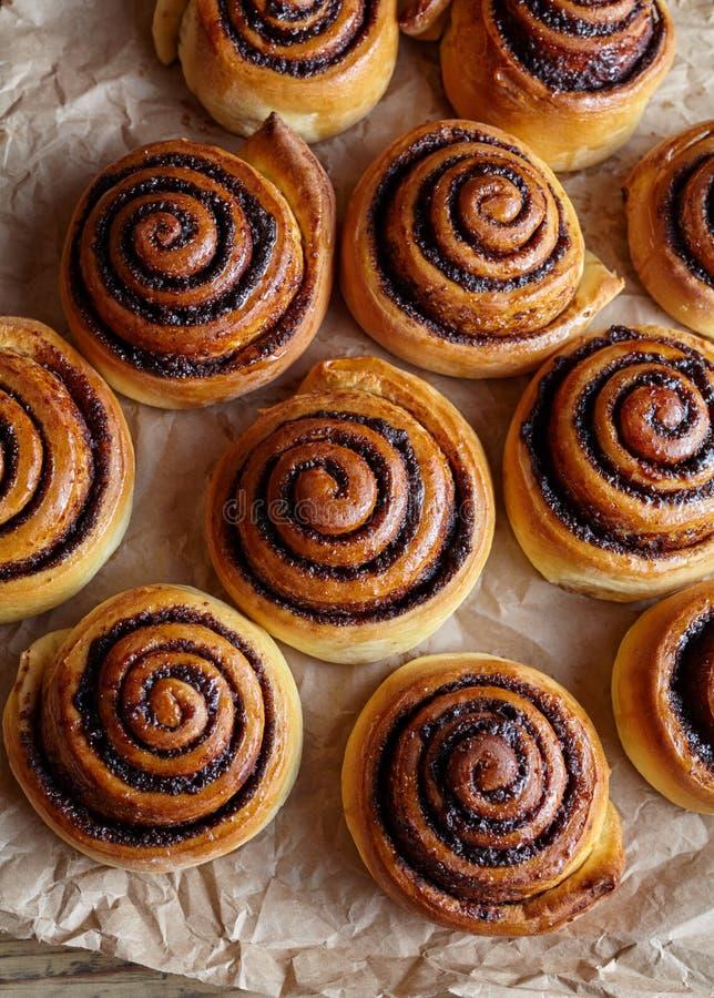 Pane del rotolo di cannella, panini, rotoli sulla carta pergamena Forno casalingo Cottura dolce di natale Kanelbulle immagini stock