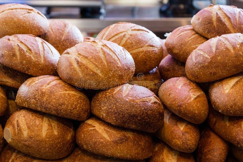 Pane di lievito naturale fresco impilato in un forno pronto a vendere e mangiare fotografia stock