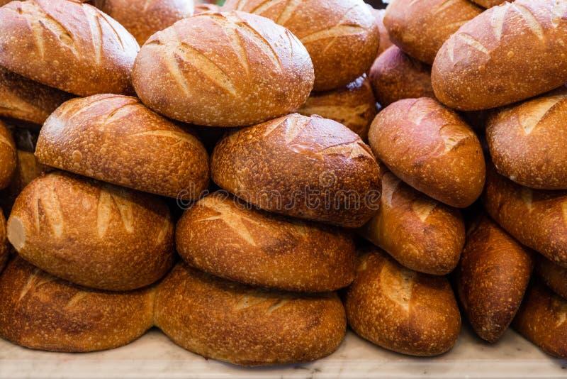 Pane di lievito naturale fresco impilato in un forno pronto a vendere e mangiare immagini stock