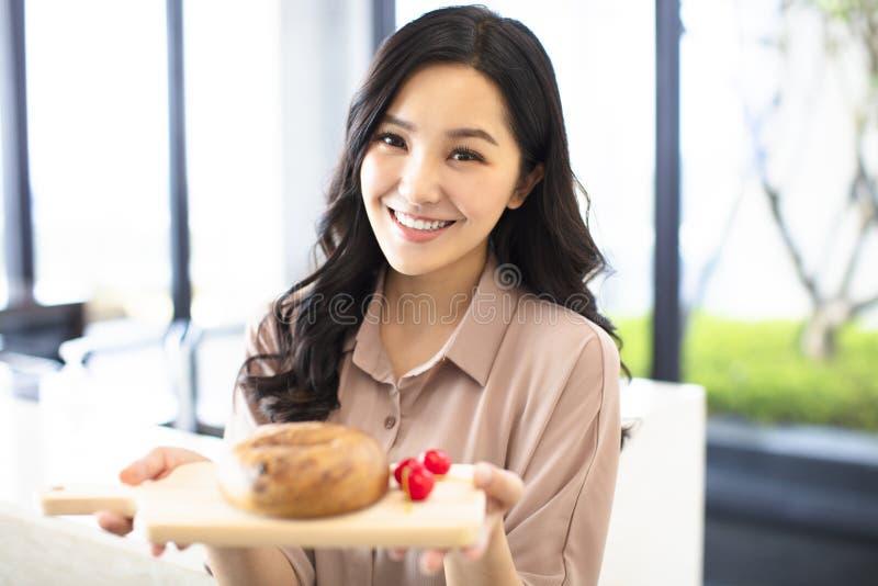 Pane di rappresentazione della giovane donna in cucina fotografia stock libera da diritti