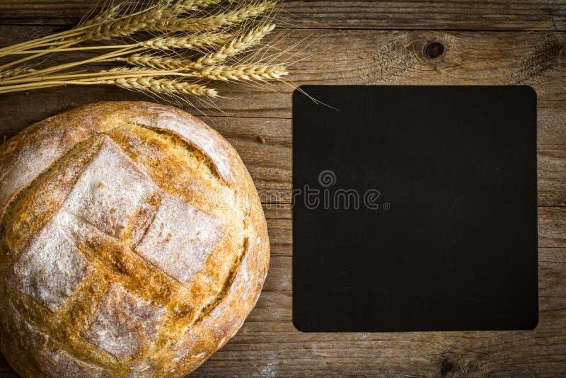 Pane di recente al forno, orecchie del grano e bordo di gesso vuoto per testo fotografie stock