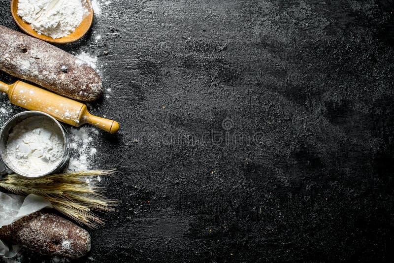 Pane di segale fragrante con farina, il matterello e le spighette immagine stock libera da diritti