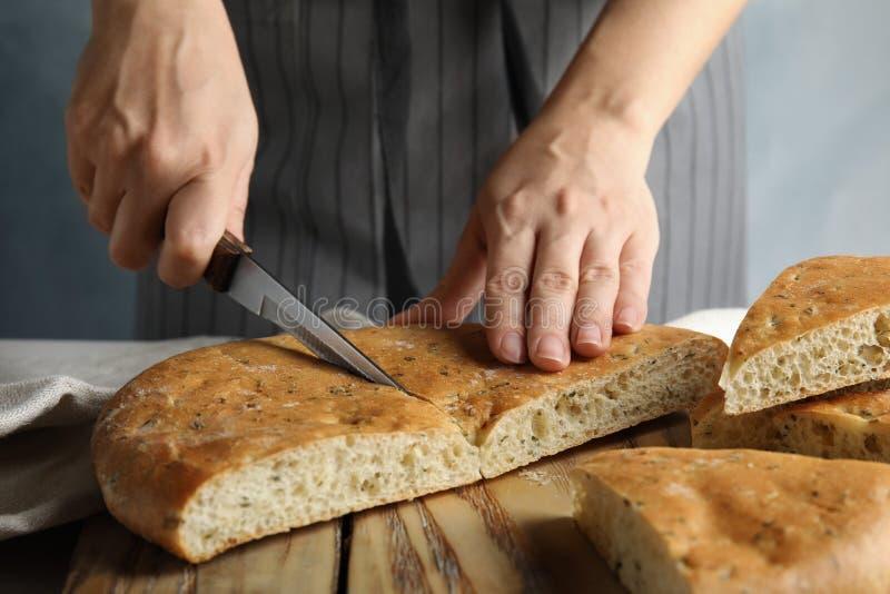 Pane di taglio della donna sul bordo di legno immagini stock