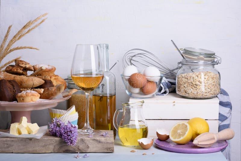 Pane e dessert con gli ingredienti del forno e un vino di vetro sul contatore di cucina domestica fotografia stock libera da diritti