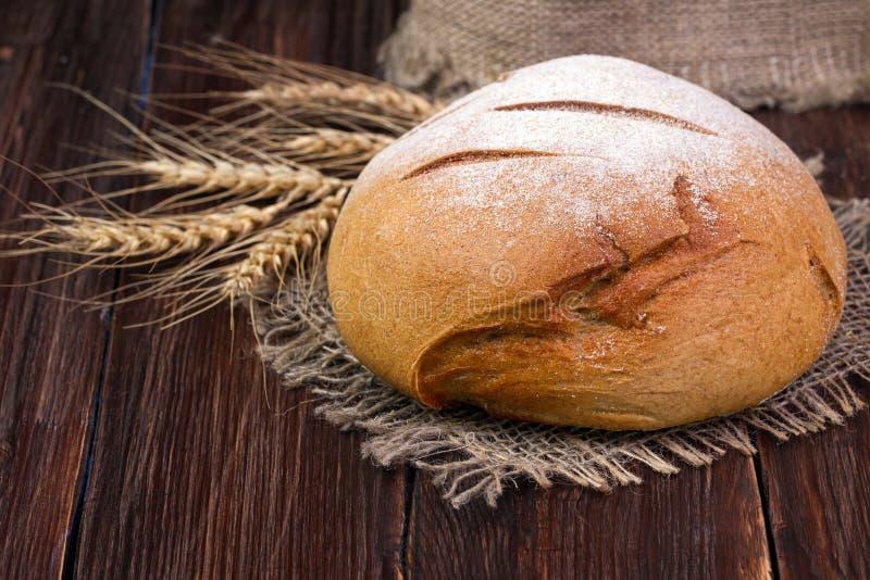 Pane e grano rotondi casalinghi sulla tavola di legno immagine stock libera da diritti