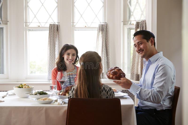 Pane ebreo del challah della tenuta dell'uomo al pasto di Shabbat con la famiglia fotografia stock libera da diritti