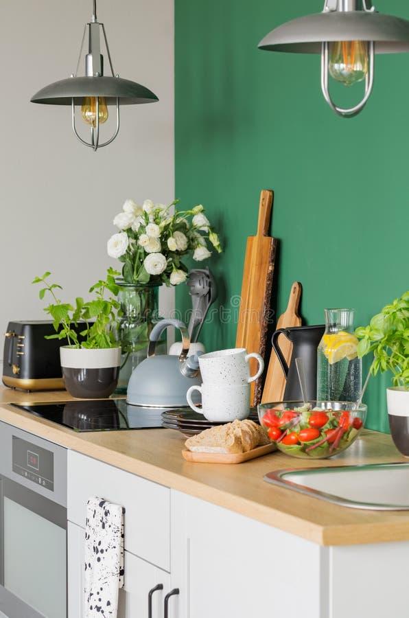 Pane ed insalata di verdure sul contatore di legno della cucina d'avanguardia immagini stock