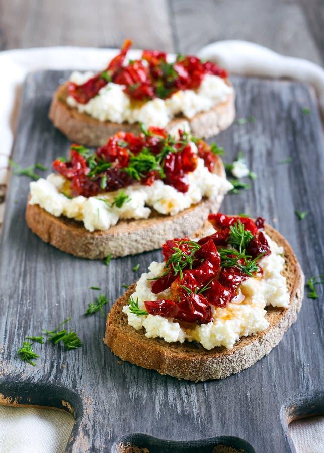 Pane fatias com queijo da ricota e, tomates secados sol imagens de stock