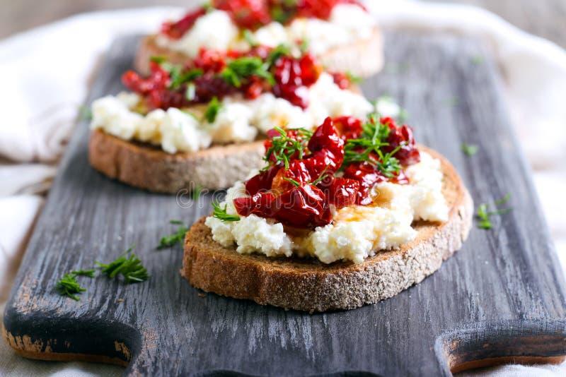Pane fatias com queijo da ricota e, tomates secados sol fotografia de stock royalty free