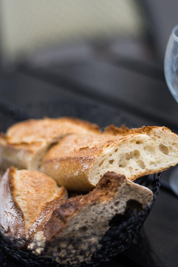 Pane francese, baguette affettate sul fondo dell'ardesia fotografia stock libera da diritti