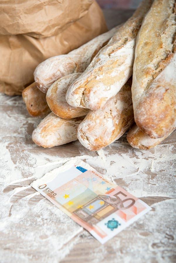 Pane francese con soldi su una tavola rustica immagine stock