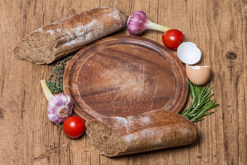 pane fresco, aglio, pomodori ed erbe sopra il tagliere del woode fotografia stock libera da diritti
