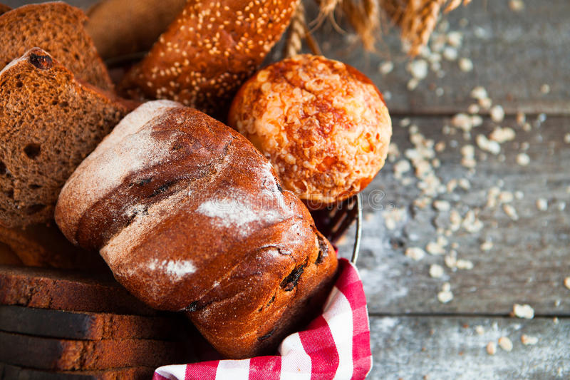 Pane fresco differente in canestro di vimini sulla tavola rustica su di legno immagini stock libere da diritti