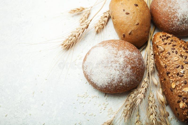 Pane integrale fresco bollente con farina e grano su una tavola bianca, vista superiore fotografia stock