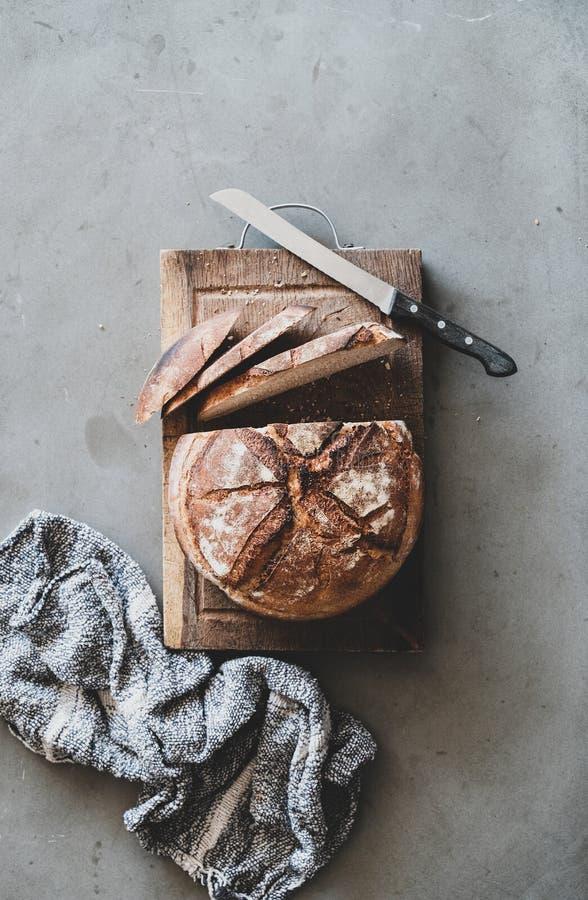 Pane intero del lievito naturale di recente al forno sul bordo di legno rustico fotografia stock