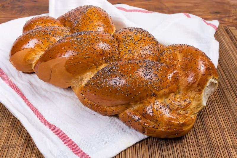 Pane intrecciato dolce con i semi di papavero sul tovagliolo fotografia stock libera da diritti